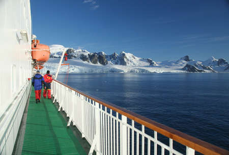 Cruise ship, icebreaker, with lifeboat, in calm seas, blue sky, with mountains & glaciers, Lemaire Channel,Antarctica
