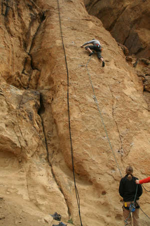 belaying: Woman belaying a climber on rock face,  Smith Rock State Park,  Central Oregon  Stock Photo