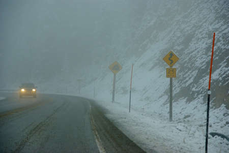 Traffic signs on icy mountain road,Rocky Mountains,Idaho  Archivio Fotografico