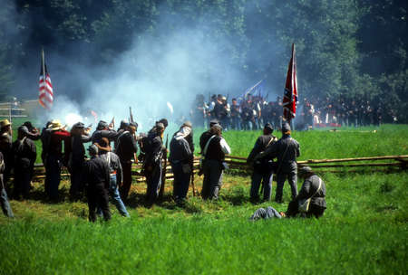 Confederates volley fire on advancing Union soldiers,		Civil War battle reenactment