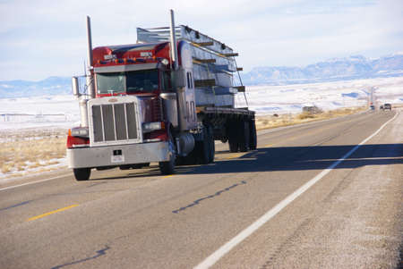 Red semi truck on winter road,   Utah