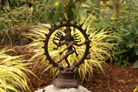 sanskrit: Bronze Shiva in garden, with blades of grass.     Nataraja (Sanskrit: Lord of Dance) Shiva represents apocalypse and creation as he dances away the illusory world of Maya transforming it into power and enlightenment.�    Stock Photo