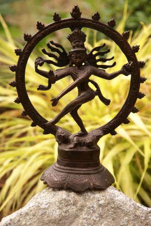 illusory: Shiva de bronce en el jard�n, con briznas de hierba. Nataraja (en s�nscrito: se�or de la danza) Shiva representa el apocalipsis y la creaci�n de lejos mientras baila el mundo ilusorio de maya transform�ndola en energ�a y la iluminaci�n. Foto de archivo
