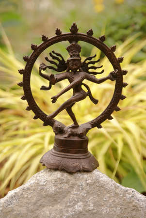Bronze Shiva in garden, with blades of grass.     Nataraja (Sanskrit: Lord of Dance) Shiva represents apocalypse and creation as he dances away the illusory world of Maya transforming it into power and enlightenment.�    photo