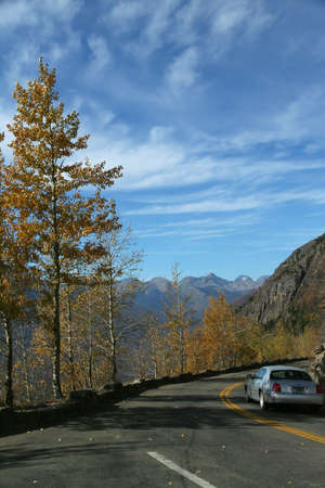 twisty: Car on narrow, twisty mountain road. Blue sky with high cirrus clouds, over mountain and autumn poplars, Glacier National Park, Rocky Mountains, Montana