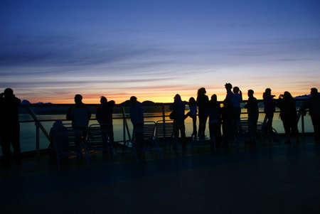 alpenglow: Watching the sunset, cruise ship passengers at bow of ship, Lynn Canal,  Alaska   Stock Photo