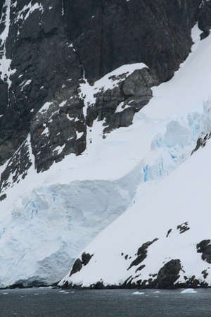 Glacier icefalls flowing  from mountains into ocean,   Lemaire Channel, Antarctica