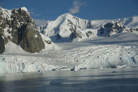icefall: Glaciated mountains and icefall at oceans edge,  Lemaire Channel, Antarctica