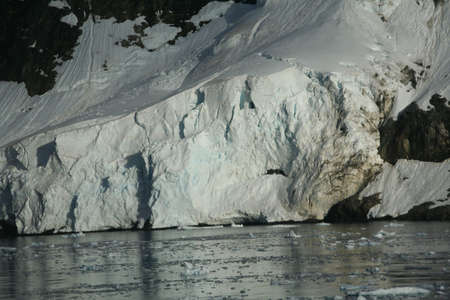 Glaciated mountains and icefall at oceans edge,  Lemaire Channel, Antarctica