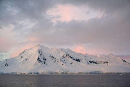 alpenglow: Subtle alpenglow lights snowy mountain,  Wilhelmina bay Antarctica