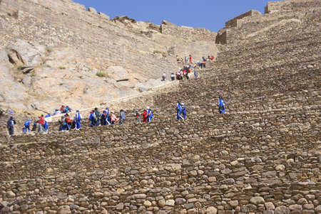 close fitting: OLLANTAYTAMBO PERU 28 AUG 2008 -   School kids in blue climbing agricultural terraces to Inca city ruins, Ollantaytambo,  Peru, South America