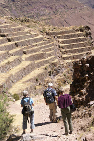 pisac: Hikers on dirt road to  terraced Inca fields and ruins of Pisac,  Cusco, Peru, South America