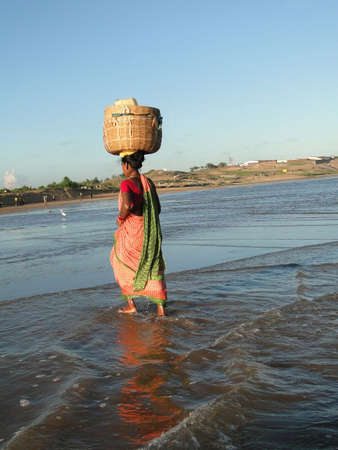 carrying: ORISSA, INDIA - NOV 14 - Orissa woman crosses tidal waters while carrying goods on her head   on Nov 14, 2009, in Puri, India.             Stock Photo