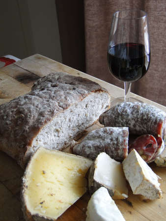 Glass of red wine, salami, cheese and whole grain bread, still life,   Chatel,  France                           photo