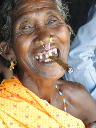 오리 사주, 인도 -11 월 10 일 - 늙은 여자는 오리 나무, 인도에서 2009 년 11 월 10 일에 부족의 마을에서 cheroot를 피우다.