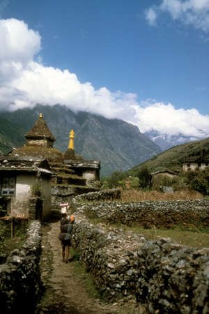 sherpa: Chortens and porter carrying load,