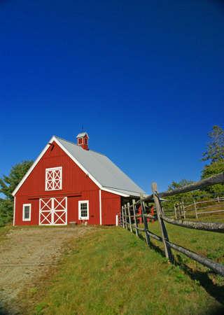 New England red barn and fence against blue sky.Mount Desert Island, Acadia National park, Maine, New England
