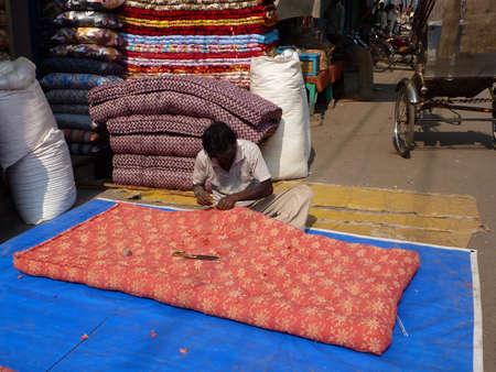 VARANASI, INDIA - NOV 7 -  Men sew large mattress covers in their shops   on Nov 7, 2009, in Varanasi, India.  Redakční