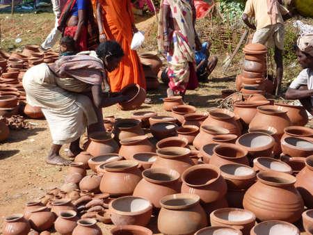 ORISSA, INDIA - NOV 11 - Tribal women buy clay pots    on Nov 11, 2009,  in Chatikona market, Orissa, India Archivio Fotografico - 7007337