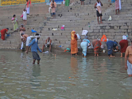 woman in bath: VARANASI, INDIA - NOV 6 - Hindus perform ritual puja at dawn in the Ganges River on Nov 6, 2009, in Varanasi, India.            Editorial