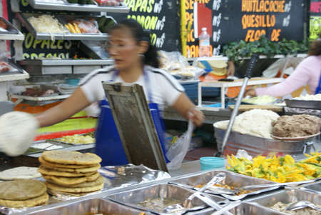 merced: MEXICO CITY - SEP 4-  Mexican woman makes quesadillas at a fast food stand on Sep 4, 2008 in the Merced Market  in Mexico City. Editorial