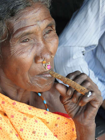 cheroot:      ORISSA,  INDIA - NOV 10  - Old woman smokes a cheroot in a tribal village  on Nov 10, 2009 in Orissa, India