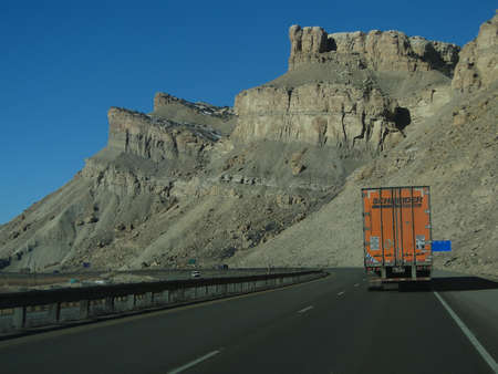 GRAND JUNCTION, COLORADO - JAN 28 - Orange semi truck drives past cliffs on Interstate I-70 near Grand Junction, Colorado                          Banco de Imagens