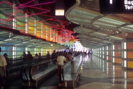 CHICAGO - 1 juni - Passagiers gebruik maken van de bewegende loopbrug onder neonlichten in het verbinden Tunnel, O'Hare Airport op 1 juni 1981 in Chicago.