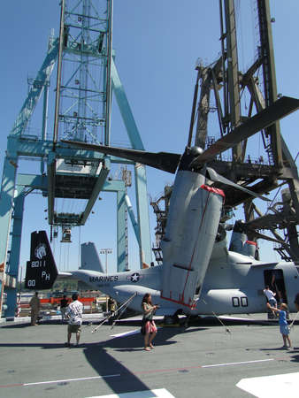 SEATTLE - AUG 4 - Civilians inspect an  MV-22 Osprey,during a tour of the Amphibious Assault Ship Bonhomme Richard, LDH-6,  on Aug 4, 2011, in Seattle. The Osprey is a military, tiltrotor aircraft with both a vertical takeoff and landing (VTOL) and short  Stock Photo - 10290293