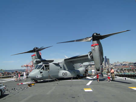 SEATTLE - AUG 4 - Civilians inspect an  MV-22 Osprey,during a tour of the Amphibious Assault Ship Bonhomme Richard, LDH-6,  on Aug 4, 2011, in Seattle. The Osprey is a military, tiltrotor aircraft with both a vertical takeoff and landing (VTOL) and short
