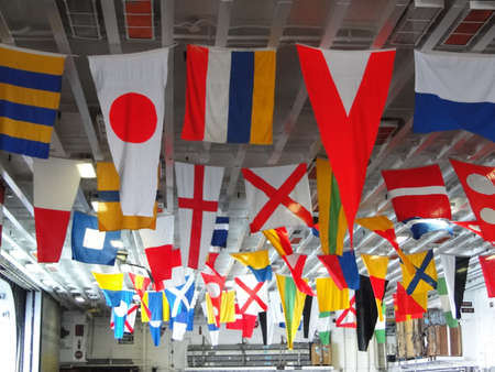 the amphibious: Signal flags displayed on the hangar deck  of Amphibious Assault Ship Bonhomme Richard, LDH-6,  docked in Seattle   Editorial