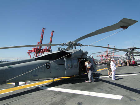 blackhawk helicopter: SEATTLE - AUG 4 - Civilians inspect an SH-60 Seahawk [variation of the armys UH-60 Blackhawk helicopter]during a tour of the Amphibious Assault Ship Bonhomme Richard, LDH-6,  on Aug 4, 2011, in Seattle.