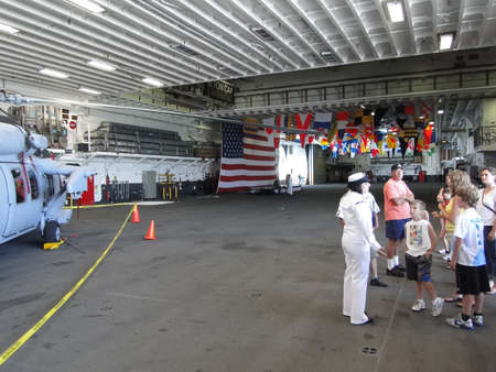 SEATTLE - AUG 4 - A Navy midshipman conducts a civilian tour   on the hangar deck  of the Amphibious Assault Ship Bonhomme Richard, LDH-6,  on Aug 4, 2011, in Seattle.