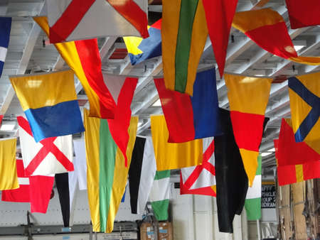 Signal flags displayed on the hangar deck  of Amphibious Assault Ship Bonhomme Richard, LDH-6,  docked in Seattle   Stock Photo