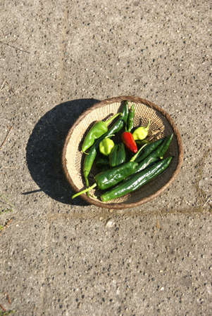 A variety of fresh green chilies in a woven basket Seattle Imagens - 11220561