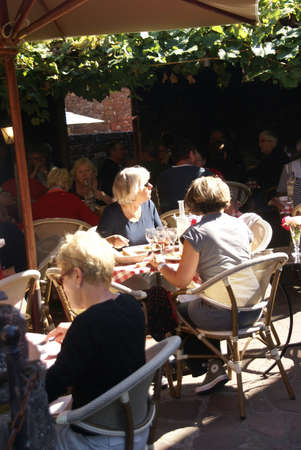 COLLONES LA ROUGE, FRANCE - SEP 22 - Tourists enjoy a relaxed lunch in an outdoor restaurant  on Sep 22, 2011  in Collones la Rouge, France