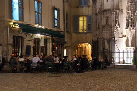 AVIGNON, FRANCE - SEP 30 -  Casual diners enjoy an evening meal near an old churchon Sep 30, 2011  in Avignon, France