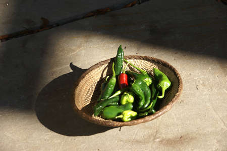 A variety of fresh green chilies in a woven basket Seattle     Imagens