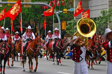 calgary: CALGARY CANADA JULY 2004 -  Cowgirls riding horses in parade, carrying flags,  Calgary Stampede, Alberta, Canada