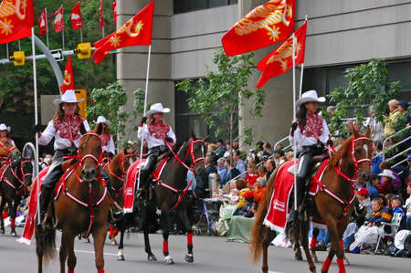 calgary stampede: CALGARY CANADA JULY 2004 -  Cowgirls riding horses in parade, carrying flags,  Calgary Stampede, Alberta, Canada