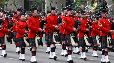 marchers: CALGARY CANADA JULY 2004 - Kilted Bagpipe players marching in  Calgary Stampede Parade Calgary Alberta, Canada