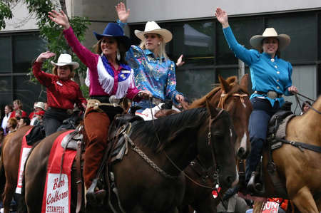 stampede: CALGARY CANADA JULY 2004 -  Cowgirls riding horses in parade, carrying flags,  Calgary Stampede, Alberta, Canada