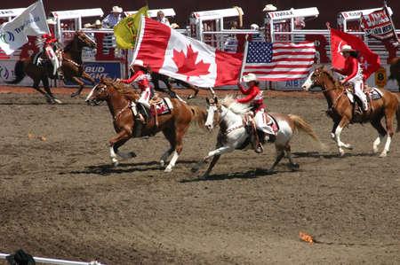 CALGARY CANADA JULY 2004 -  Cowgirls galloping on horseback, carrying flags,  Calgary Stampede, Alberta, Canada