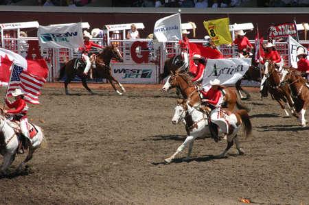 stampede: CALGARY CANADA JULY 2004 -  Cowgirls galloping on horseback, carrying flags,  Calgary Stampede, Alberta, Canada Editorial