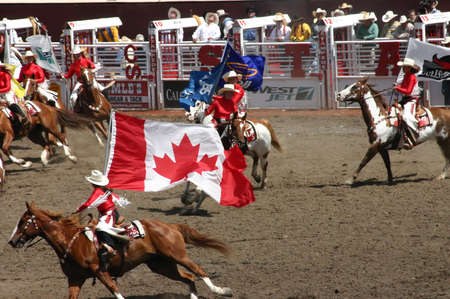 calgary stampede: CALGARY CANADA JULY 2004 -  Cowgirls galloping on horseback, carrying flags,  Calgary Stampede, Alberta, Canada Editorial