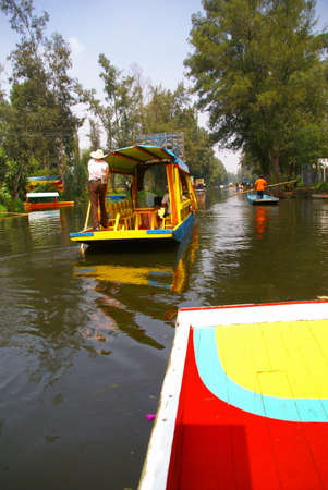 poling: Boatman poling brightly colored boat,  Xochimilco canals, floating gardens,  Mexico City Editorial