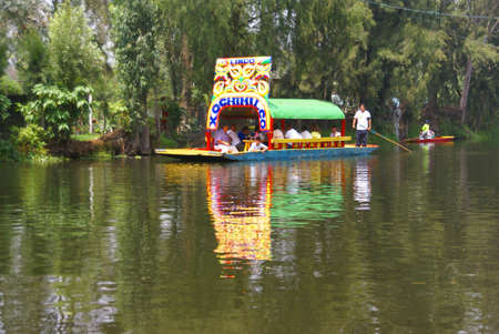 poling: Xochimilco Mexico City  3 SEP 2008 -  Boatman poling brightly colored boat, Xochimilco canals, floating gardens,  Mexico City Editorial