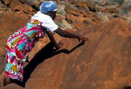 Twyfelfontein, NAMIBIA JUL 1995 -  Namibian woman showing prehistoric carvings [petroglyphs]   Namibia, Africa Editorial