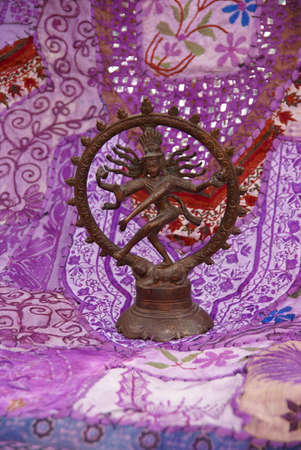 sanskrit: Bronze Shiva on purple - lavendar Rajasthani textile backdrop made from saris.    Nataraja (Sanskrit: Lord of Dance) Shiva represents apocalypse and creation as he dances away the illusory world of Maya transforming it into power and enlightenment.�   Editorial