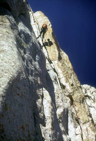 abseil: Climber on rappel from Pingora,   Wind Rivers Range of Rocky Mountains Wyoming Stock Photo